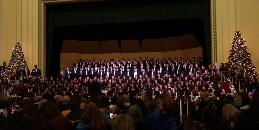 Choir students of every level fill the stage between two Christmas trees funded by Limeades for Learning.