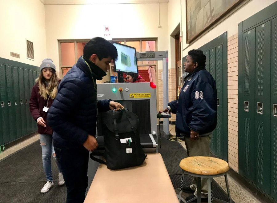 Security guard Mrs. Jackson examining students' bags with an X-Ray baggage scanner to check for any potentially dangerous objects. Every day after 8:15, all students' bags are checked.