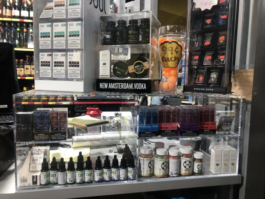 A display of vaping products at a gas station, including JUUL vape pens.