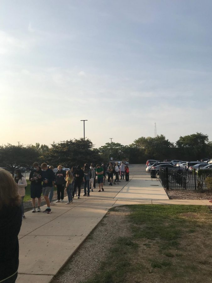 Students wait to enter Lane in order to take the Sept. 23 SAT. There were no markers on the ground delineating six feet, nor many teachers or parent volunteers keeping students socially distant.
