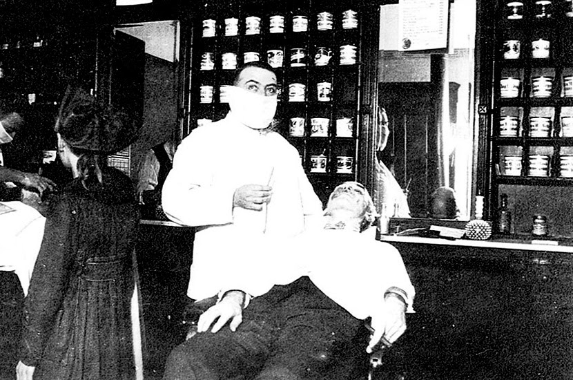 A masked barber poses for a photo as he shaves a patron. Cincinnati Ohio, 1918 (CDC)
