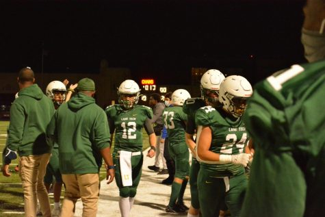 Quarterback Mark Seward (#12) walking to the sidelines from the field.
