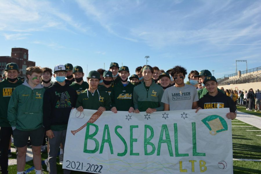 The baseball team pictured with their sign.