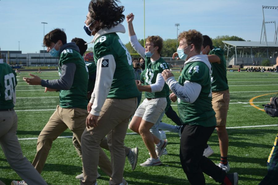 The football team rushing to cheer on the winners of homecoming court.