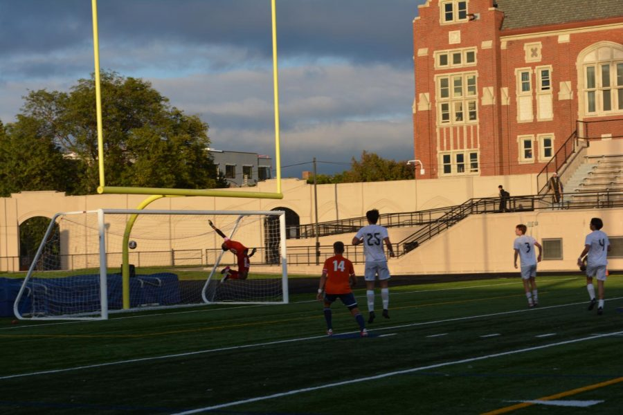 Goalkeeper Jeremiah Higgins in midair jumping for the ball while it shoots past him and into the net.
